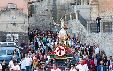 Procession to mark the Festival of San Giorgio bearing the mounted figure of St. George into Ragusa Ibla, Ragusa, Sicily, Italy, Europe