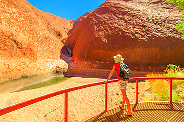 Tourist woman with wide hat standing at balcony and admires Mutitjulu Waterhole at the end of short Kuniya walk in Uluru-Kata Tjuta National Park. Tourism in Northern Territory, Central Australia.