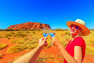 Lifestyle woman doing cheers to celebrate at Uluru Ayers Rock at sunset in Uluru-Kata Tjuta National Park. Blonde traveler in Australian outback Red Centre. Tourism in Northern Territory, Australia.