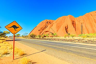 Kangaroo crossing sign warning drive along Ayers Rock in Uluru-Kata Tjuta National Park, Northern Territory, Red Centre, Central Australia. Australian outback landscape in dry season.