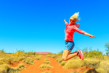 Happy tourist woman jumping at Uluru Ayers Rock in Uluru-Kata Tjuta National Park. Lifestyle traveler enjoying in Australian outback Red Centre. Tourism in Northern Territory, Central Australia.