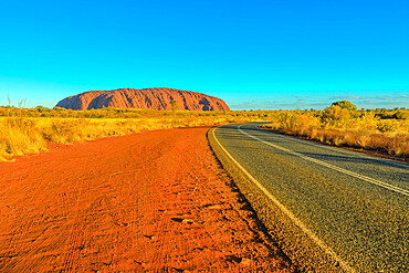 Road leading to Uluru Ayers Rock at vibrant color of sunset. The huge sandstone monolith icon of Australian outback in Uluru-Kata Tjuta National Park. Central Australia, Northern Territory. Copy space