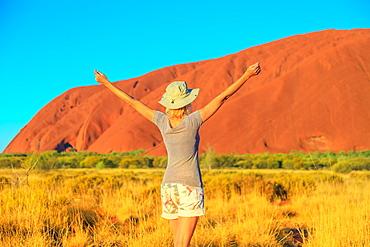 Carefree tourist woman with raised arms enjoys Uluru (Ayers Rock) at sunset in Uluru-Kata Tjuta National Park, UNESCO World Heritage Site, Northern Territory, Australia, Pacific