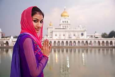 A young woman worshipping at a Sikh temple in Delhi, India, Asia