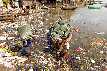 Two men unloading sacks of produce from a small boat in Sittwe harbour, wading through polluted water full of plastic rubbish, Sittwe, Rakhine, Myanmar (Burma), Asia