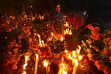 Zapotec woman holding candle among graves adorned with marigolds, Atzompa, Oaxaca, Mexico, North America