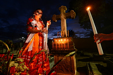 Girl wearing traditional dress and with face painted as catrinal holding candle in graveyard, Xoxocotlan, Oaxaca, Mexico, North America