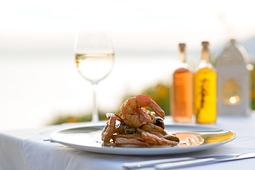 Prawns with white wine at sunset at a restaurant in Pefkos, Rhodes, Dodecanese, Greek Islands, Greece, Europe