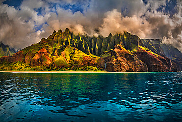 The Cathedral of the NaPali Coastline towers over the calm summer waters at sunset.