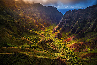 Flying through Nu'alolo Valley via helicopter in the evening on the NaPali Coastline. Kauai, Hawaii