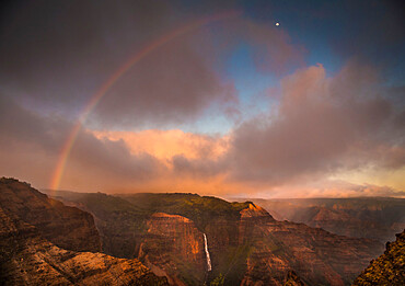 Sunset rainbow arches over the Waimea Canyon and Waipo'o Falls towards the moon. Kauai, Hawaii
