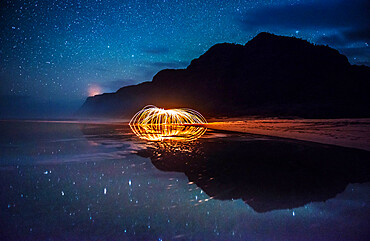Polihale State Park under a starry sky with sparks being reflected in a tidal pool.