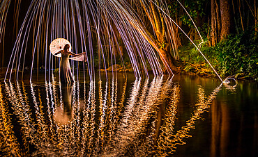 A young woman in a white dress standing in a river at night extends her hand to catch a falling spark.