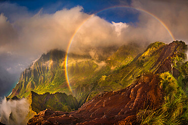 A 180 degree rainbow is formed by the clouds over the Kalalau Valley on Kauai's west coast in the evening.