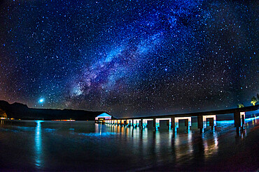 The Milky Way and Venus rise over the Hanalei Bay with the Hanalei Pier in the foreground lit by passing car headlights.