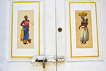 Afro-Brazilian paintings in a white wooden door at Travessa do Comercio, Brazil