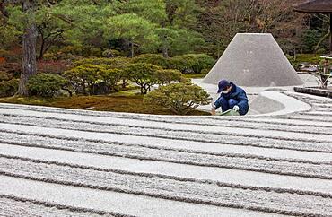 Gardener working,Zen garden symbolizing Mount Fuji and the sea, in Ginkaku ji temple, Kyoto, Kansai, Japan