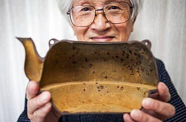 Nizaemon Koizumi shows the rusty of inside in a iron teapot or tetsubin, nanbu tekki, Workshop of Koizumi family,craftsmen since 1659, Morioka, Iwate Prefecture, Japan