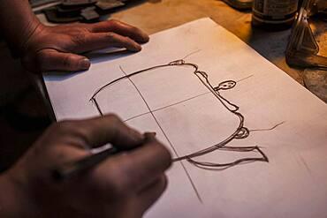 Takahiro Koizumi is designing a iron teapot or tetsubin, nanbu tekki,Workshop of Koizumi family,craftsmen since 1659, Morioka, Iwate Prefecture, Japan