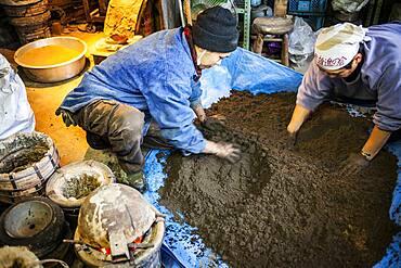 Takahiro Koizumi at right and his assistant kohei ishimori at left  are making mud to build a molds to make a iron teapot or tetsubin, nanbu tekki,Workshop of Koizumi family,craftsmen since 1659, Morioka, Iwate Prefecture, Japan
