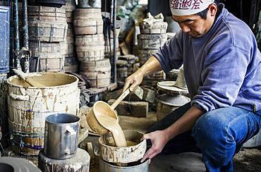 Takahiro Koizumi is sifting water to make mud, and build a molds to make iron teapot or tetsubin, nanbu tekki, Workshop of Koizumi family,craftsmen since 1659, Morioka, Iwate Prefecture, Japan
