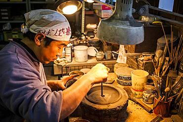 Takahiro Koizumi is making the outer mold of a new design of a iron teapot or tetsubin, nanbu tekki,Workshop of Koizumi family,craftsmen since 1659, Morioka, Iwate Prefecture, Japan