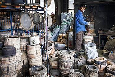 Kohei ishimori is preparing the fire with coal, for baking the molds, to resist the molten iron and make a iron teapot or tetsubin, nanbu tekki,Workshop of Koizumi family,craftsmen since 1659, Morioka, Iwate Prefecture, Japan