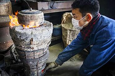 baking the outer mold, to resist the molten iron and make a iron teapot or tetsubin, nanbu tekki,Workshop of Koizumi family,craftsmen since 1659, Morioka, Iwate Prefecture, Japan