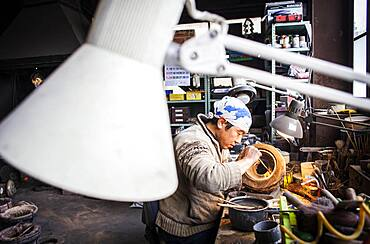 Takahiro Koizumi is making the outer mold of a new design of a iron teapot or tetsubin, nanbu tekki, Workshop of Koizumi family,craftsmen since 1659, Morioka, Iwate Prefecture, Japan