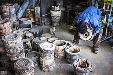 Kohei ishimori checks that the outer molds are properly cooked, to resist the molten iron and make a iron teapot or tetsubin, nanbu tekki,Workshop of Koizumi family,craftsmen since 1659, Morioka, Iwate Prefecture, Japan