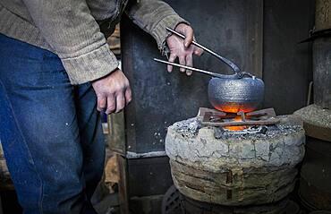 Takahiro Koizumi is putting the finishing touches at iron teapot or tetsubin, nanbu tekki,Workshop of Koizumi family,craftsmen since 1659, Morioka, Iwate Prefecture, Japan