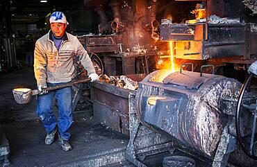 Takahiro Koizumi carries molten iron with spoon to pour it into the mold, to make a iron teapot or tetsubin, nanbu tekki, Workshop of Koizumi family,craftsmen since 1659, Morioka, Iwate Prefecture, Japan