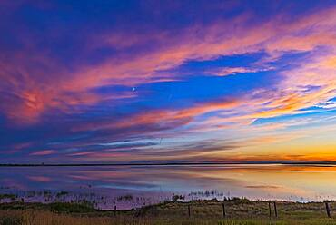 Sunset colours over Deadhorse Lake in southern Alberta, on July 8, 2016. The waxing crescent Moon shines amid the colourful clouds.