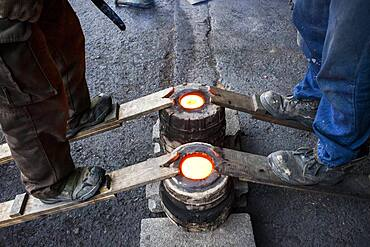 Takahiro Koizumi and his assistant Kohei ishimori are waiting that solidify the molten iron inside the molds, to make a iron teapot or tetsubin, nanbu tekki,Workshop of Koizumi family,craftsmen since 1659, Morioka, Iwate Prefecture, Japan