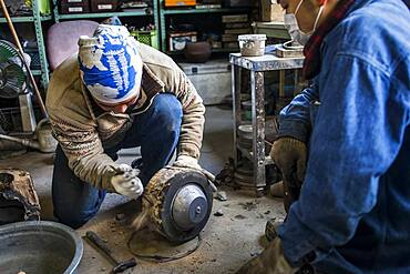 Takahiro Koizumi is breaking the mold just  after solidifying the molten iron. He casts the first look at new iron teapot or tetsubin, nanbu tekki, Workshop of Koizumi family,craftsmen since 1659, Morioka, Iwate Prefecture, Japan