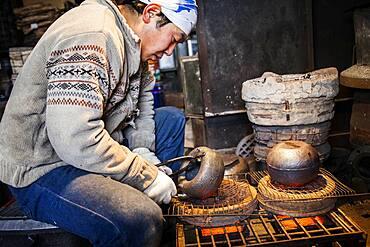 Takahiro Koizumi is putting the finishing touches at iron teapots or tetsubin, nanbu tekki,Workshop of Koizumi family,craftsmen since 1659, Morioka, Iwate Prefecture, Japan