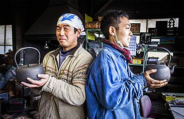 Takahiro Koizumi at left and his assistant at right  are showing their finish work, iron teapots or tetsubin, nanbu tekki,Workshop of Koizumi family,craftsmen since 1659, Morioka, Iwate Prefecture, Japan