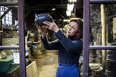 Morihisa Suzuki is reviewing the quality of work in a new iron teapot or tetsubin , the only woman who has made iron teapots in the nearly 400 years of history that has molten iron crafts in Iwate, in Workshop of Morihisha Suzuki,craftsmen since 1625, nanbu tekki, Morioka, Iwate Prefecture, Japan