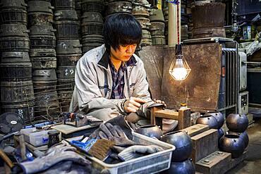craftsman is putting the finishing touches at iron teapot or tetsubin, nanbu tekki, in Workshop of Morihisha Suzuki,craftsmen since 1625, Morioka, Iwate Prefecture, Japan