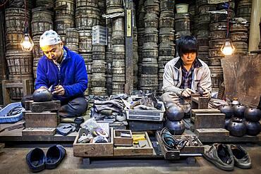 artisans are putting the finishing touches at iron teapots or tetsubin, nanbu tekki, in Workshop of Morihisha Suzuki,craftsmen since 1625, Morioka, Iwate Prefecture, Japan