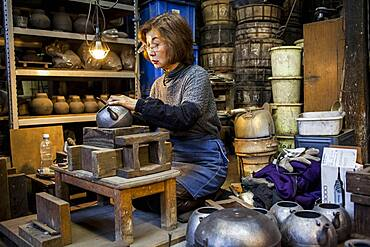 Morihisa Suzuki  is putting the finishing touches at iron teapot or tetsubin, the only woman who has made teapots in the nearly 400 years of history that has molten iron crafts in Iwate, in Workshop of Morihisha Suzuki,craftsmen since 1625, nanbu tekki, Morioka, Iwate Prefecture, Japan
