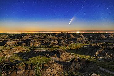 This is Comet NEOWISE (C/2020 F3) over the Horseshoe Canyon formation near Drumheller, Alberta on the night iof July 10-11, 2020, taken about 2 a.m. MDT with the comet just past lower culmination with it circumpolar at this time. Warm light from the rising waning gibbous Moon provides the illumination. The comet's faint blue ion tail is just barely visible even in the moonlit sky and low altitude.  The glow of summer perpetual twilight at latitude 51.5�8 N still colours the northern horizon despite this being close to the middle of the night.