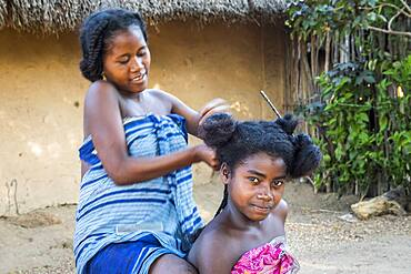 Young girls, friends arranging their hair, small town in the Tsingy de Bemaraha National Park. Madagascar, Africa