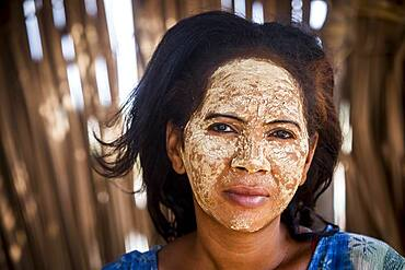 woman with traditional face mask, in Morondava, Madagascar, Africa