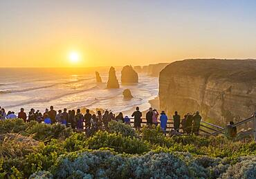 Tourists watching and photographing the sunset at the first and main Twelve Apostles viewpoint, on the Great Ocean Road, Australia.