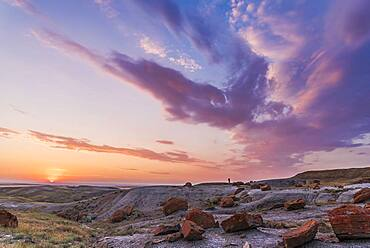 A particularly colourful sunset at the Red Rock Coulee Natural Area in southeast Alberta, with a lone figure silhouetted against the sky.