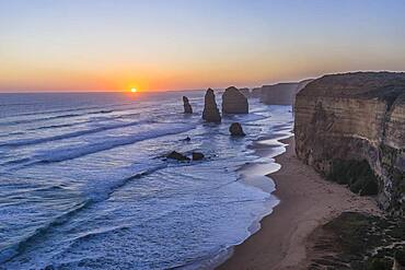 The setting Sun at the Twelve Apostles sea stacks and cliffs on the Great Ocean Road, on April 12, 2017.