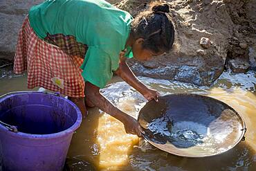 Girl miss school to pan for gold in the mountains near Ankavandra, Madagascar
