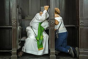 woman and priest, confession, in Basilica of Our Lady of Candelaria, Medellín, Colombia