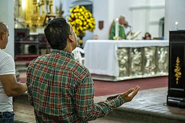 Man praying, in Basilica of Our Lady of Candelaria, Medellín, Colombia